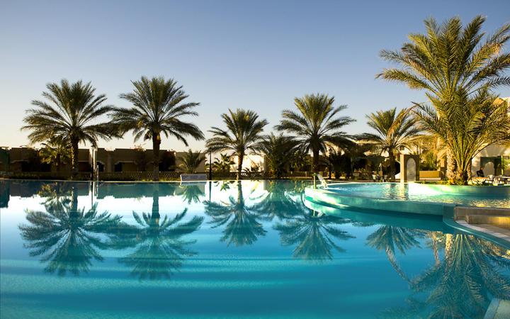 Palmen an einem luxoriösen Pool in Djerba © parkisland / Shutterstock.com